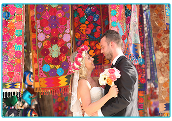 How to plan your wedding abroad on a budget - happy couple in a colourful bazaar or market