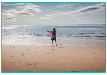 Why are Brits buying more caravans? - Girl enjoys freedom of caravanning on a beach.