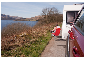 Why are Brits buying more caravans? - man sits in camping chair at side of the road drinking tea.
