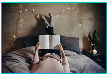 Reasons you can't get a good night's sleep - person reading book in bed.