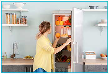 save energy in the home - woman looking in fridge