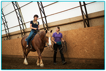 Am I too old to learn to ride a horse? - Instructor leading student indoors