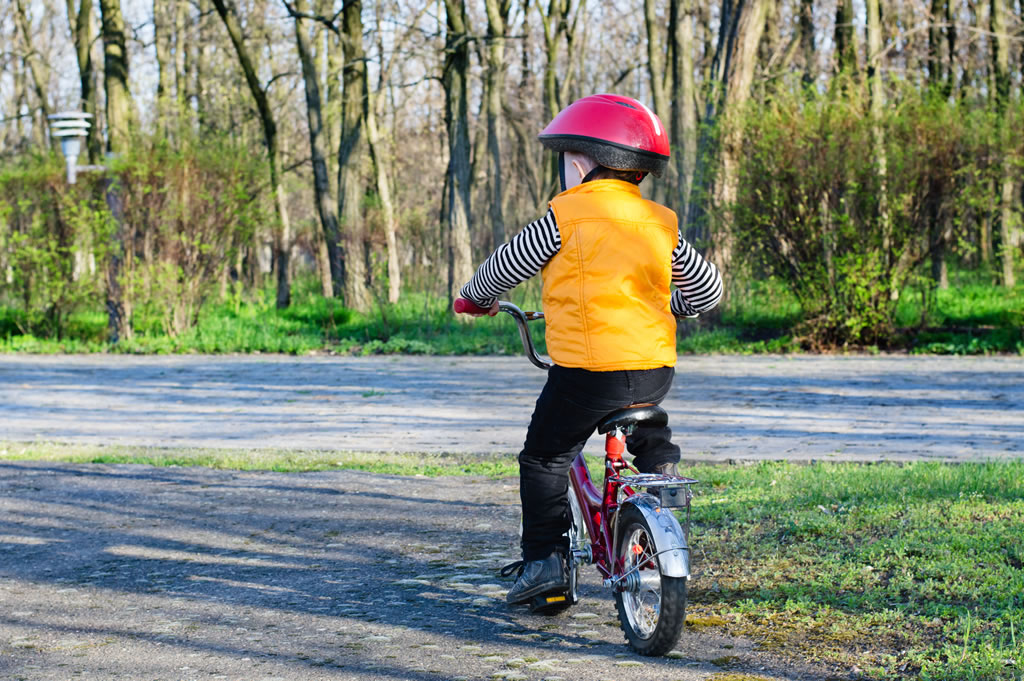 Child riding bicycle in helmet