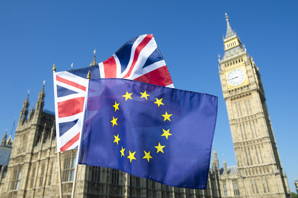 Union Jack and EU flags flying in front of The Houses of Parliament